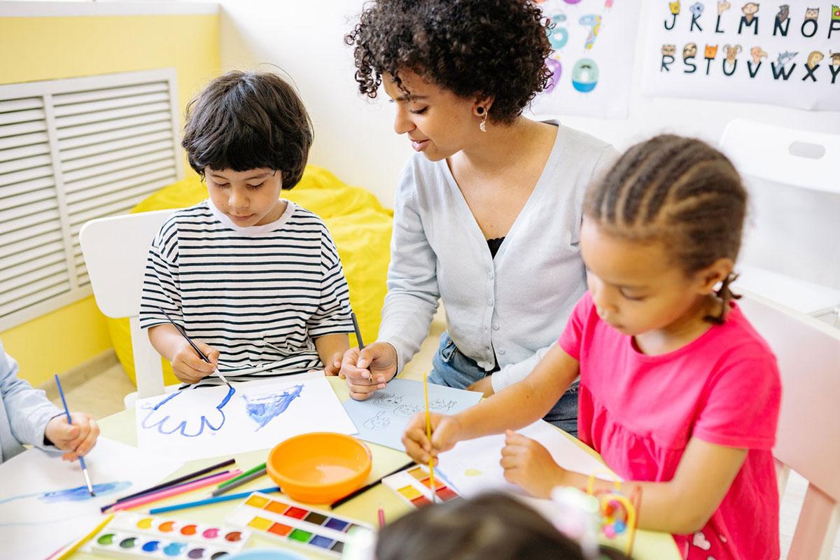 preschool students painting with teacher